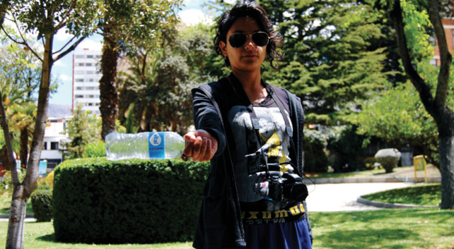 A young Latina artist wearing sunglasses and a camera around her neck is pictured outside with a plastic water bottle in hand, facing the camera as if to show the water bottle off; she stands in front of a verdant background.