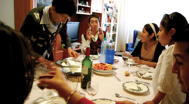 Multi-generational group of Bolivians living or visiting Pamplona, Spain are gathered around a dining table, covered with a white tablecloth, food, wine, and drinking water, are engaged in laughter and dialogue.