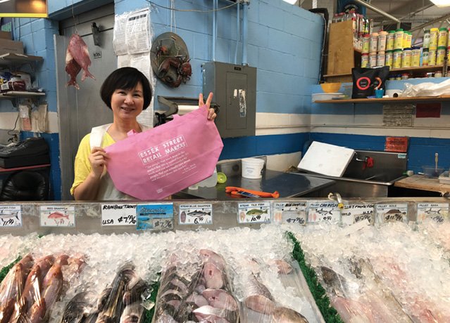 A middle-aged East Asian woman, with a short bob, stands holding a pink Essex Street Market Tote in front of a fish market stand. The woman gestures a peace sign with her left hand.