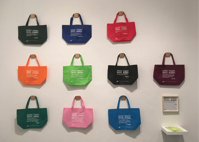 Ten multicolored Essex Street Market Totes are showcased, hanging on a white wall, with a description off the right side.