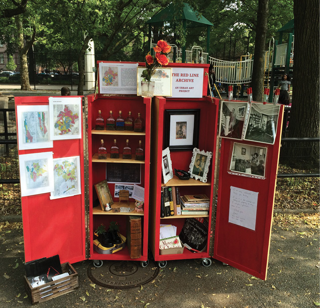 Pictured here is artist Walis Johnson's Red Line Archive. A mobile cabinet is displayed in a park; the cabinet is painted and appears with open doors; inside are objects like maps, framed photos, shoes, books and liquors that represent the pre-gentrified Black population of Brooklyn, NY. Atop the cabinet are flowers setting in a cup.