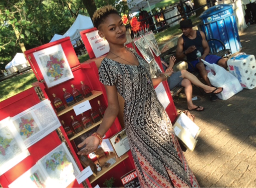 This is a photo of a young Black woman with short-cropped natural hair. This woman is wearing a long dress and she is pictured modeling in front of the Red Line Archive.