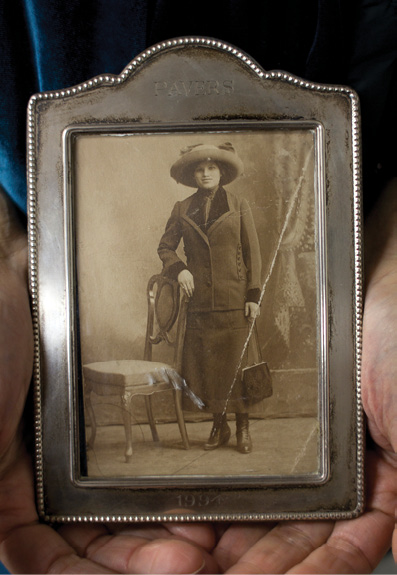 The hands of Suzanne Pred Bass hold an antique framed black-and-white image of her great aunt Rosie Weiner, an older white woman wearing a dark grey suit with a black blouse and a wide brim grey hat from the 1930s.