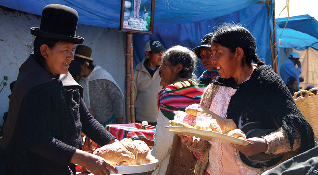 Pictured here is a market scene where an indigenous woman in La Paz, Bolivia purchases fresh bread from an indigenous Bolivian man. Other indigenous people are also shopping in the background.